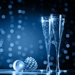 Fototapete - Two glasses of champagne with Christmas toys. Festive lights bokeh Christmas background. New Year holidays celebration. Square
