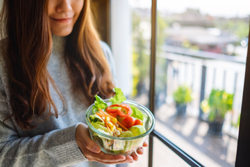 Closeup image of an asian woman holding a bowl of fresh mixed vegetables salad