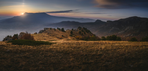 Sun hides behind the mountains. Beautiful sunrise or sunset. Scenic view Fotomurales