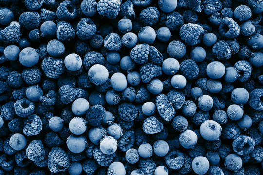 Frozen berries toned in classic blue color, top view. Close up.