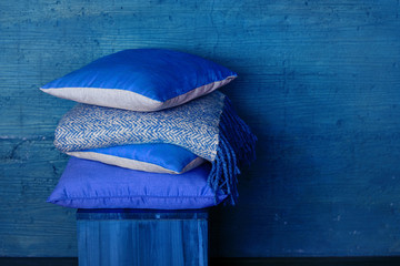 Pillows on chair against blue wall.