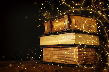Obraz stack of antique books on old wooden table. fantasy medieval period and religious concept. Glitter sparkle lights - fototapety do salonu