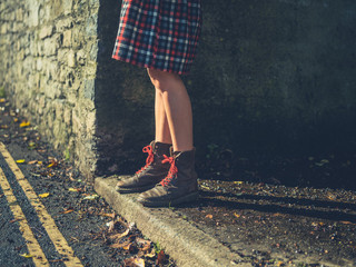 The legs of a young womn standing by the roadside