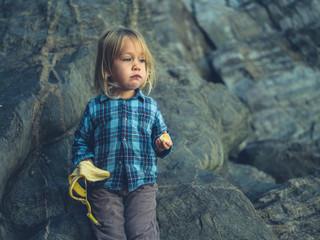 Little toddler eating banana by rocks