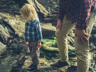 Father and son walking on rocky ground by the coast