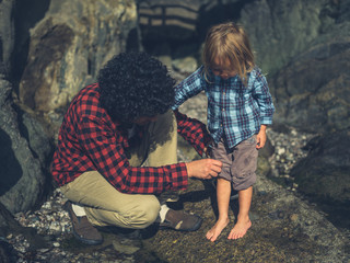 Father helping toddler roll up pants