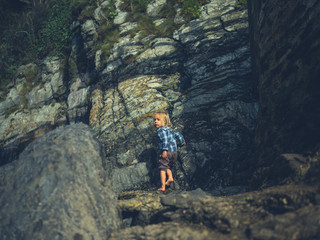 Little toddler by rocks on the coast