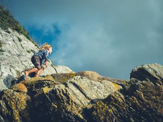 Little toddler climbing rock on the coast