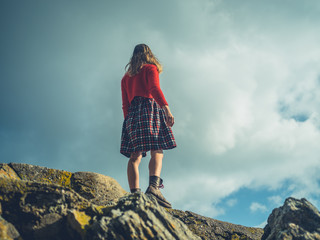 Young woman standing on top of rock against blue sky
