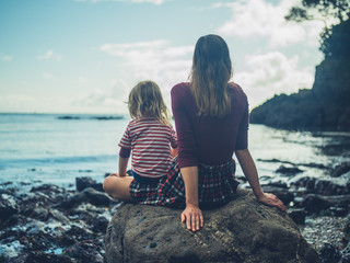 Mother and toddler sitting on a rock by the sea
