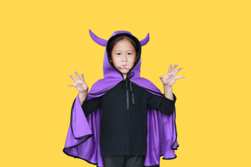Portrait little girl dressed Halloween costume with face make up. Kid in Dracula robe with frightening expression isolated on yellow background. Wall mural