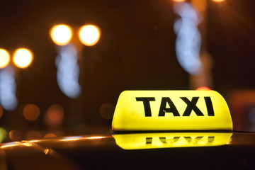 An yellow taxi sign at night