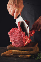 Male butcher cuts raw beef meat.
