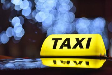 An yellow taxi sign at night