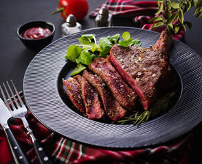 Steak on the bone. Rib eye. Tomahawk steak on the black plate with rosemary. Roasting - Rare. Entrecote