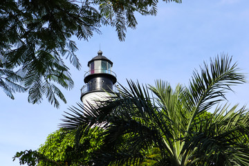 Framed by trees, the upper portion of the Key West Historic lighthouse, originally built in 1848 and reconstructed in 1894 to stand over 100 feet tall.