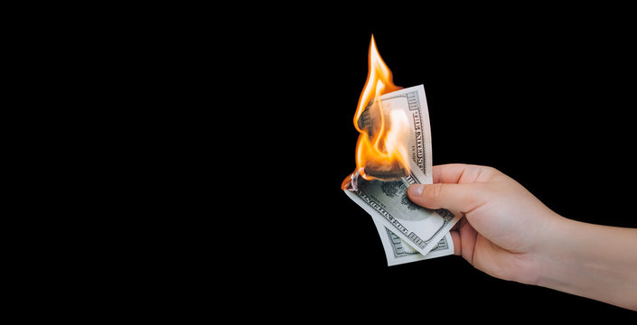 Human hand holding a burning 100 dollar bill. Black background. Close up, copy space.