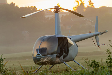 Foto op Plexiglas Helicopter Helicopter Aircraft Silver Open Four Seater Dawn Grass Field