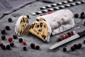 Slice of traditional German christmas season sweet food called 'Stollen' or 'Christstollen', a fruit bread of nuts, spices, and dried or candied fruit, coated with powdered sugar