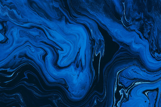 Hand painted background with mixed liquid blue and golden paints. Classic blue color of the year 2020. Abstract fluid acrylic painting. Marbled blue abstract background. Liquid marble pattern