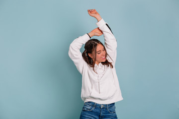 Charming lovable woman with dark hair wearing white pullover smiling with closed eyes and pulling hands up isolated over blue background