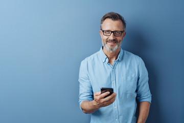 Smiling friendly man holding his mobile phone Papier Peint