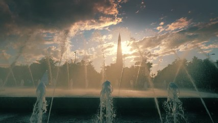 Fototapete - City skyline seen through water fountain in Saint Petersburg, Russia at sunset. Slow motion, 4K UHD.