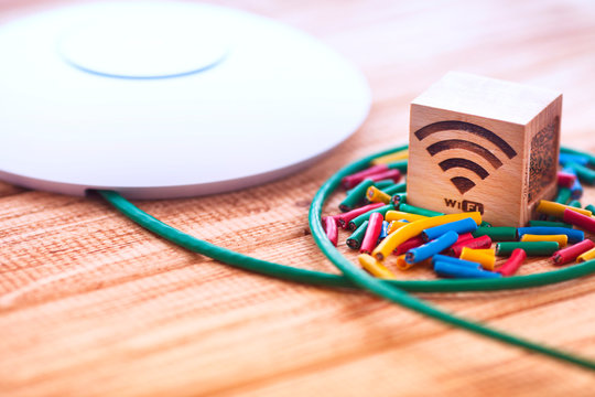 Access point with bright cables connected on it on the wooden background. Space for your text.