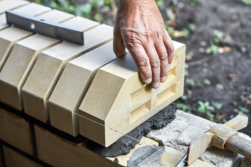 Bricklayer installing bricks on the new fence from facing bricks.