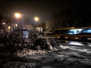 Picture of a road covered in snow and trees with a yellow motion-blurred bus on  the background