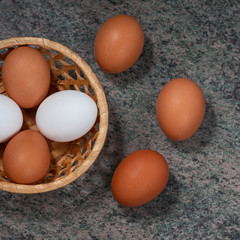 several fresh chicken eggs in a straw basket on a wooden background. Healthy eating concept.