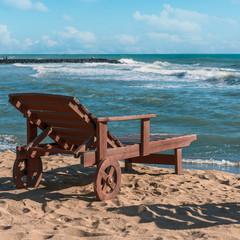 deck chair on a sunny sandy beach amid the oncoming waves of the Tyrrhenian Sea