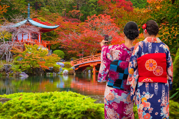 Women in traditional japanese kimonos watching amazing tempe in Kyoto at autumn. Japan