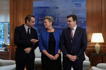 Greek Prime Minister Kyriakos Mitsotakis speaks with EU Commission Vice President Margaritis Schinas and Commissioner for Home Affairs Ylva Johansson as they pose for a picture at the Maximos Mansion in Athens