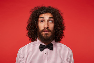 Close-up of amazed young brunette curly man with beard looking to camera with wide eyes opened and wrinkling forehead, wearing checkered shirt and black bow-tie over red background Wall mural