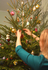 Girl decorating Christmas Tree in the House with Colorful Christmas Balls Decoration.