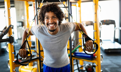Man training with trx fitness straps in the gym. Workout healthy lifestyle sport concept