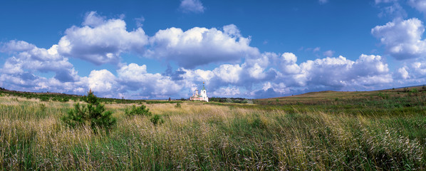 Church in the field against the blue sky with clouds. Luhansk region, Ukraine