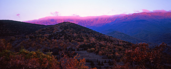 Panoramic view of the Crimean mountains with pink clouds at sunset in autumn.