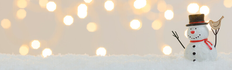 banner with many different christmas items on white snow with many small, shining lights in the background