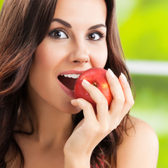 Young happy smiling lovely brunette woman with red apple