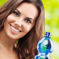 Portrait of young smiling lovely brunette woman with bottle of water, outdoor. Healthy lifestyle, beauty and dieting concept.