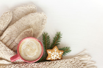 pink mug with foamy drink and ginger Christmas star, mittens and scarf on a table top view. warming coffee in the atmosphere of winter holidays