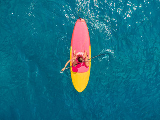 Attractive woman in swimwear floating on stand up paddle board on a quiet blue ocean. Sup surfing in tropical sea