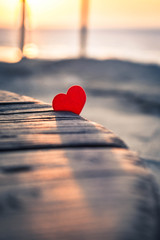 Small red heart in the rays of the setting sun on an old wooden surface. Tender picture with a red heart on the beach. A little red heart lit by the setting sun casts a shadow on the old wood.