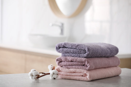 Stack of fresh towels and cotton flowers on table in bathroom