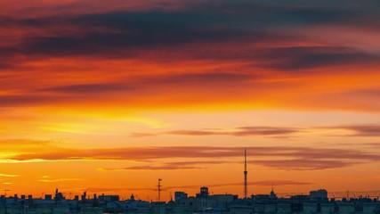 Fotobehang - Epic sunset clouds in orange sky over city skyline. Saint Petersurg, Russia. Timelapse, 4K UHD.