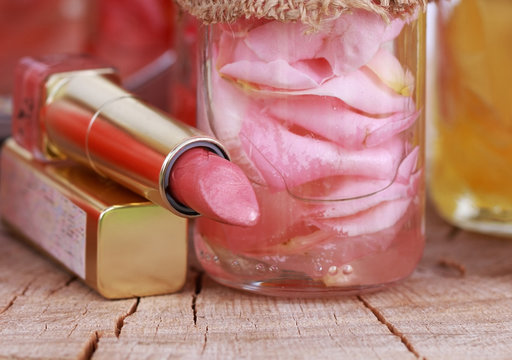 Close up, Pink delicate rose oil and pink lipstick, perfect cosm