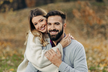 Young loving couple enjoying embraced in autumn day and looking at camera