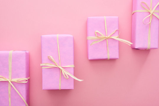 top view of wrapped presents with bows on pink